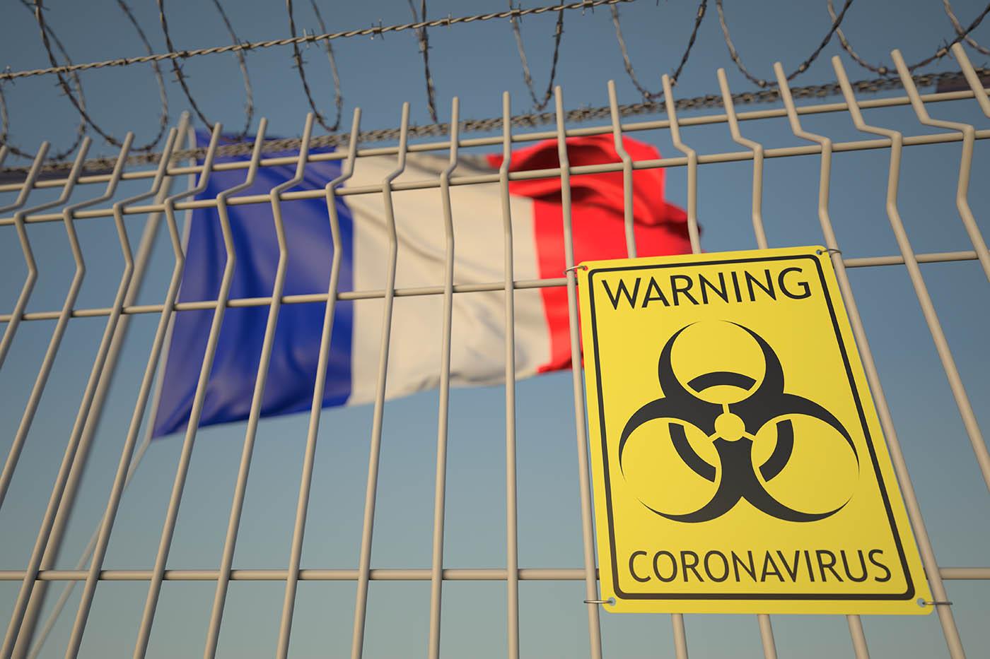 French flag behind bars with coronavirus warning sign
